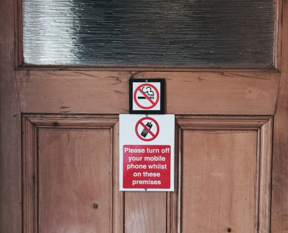 A sign on the door to a pub that says 'Please turn off your mobile phone whilst on these premises'